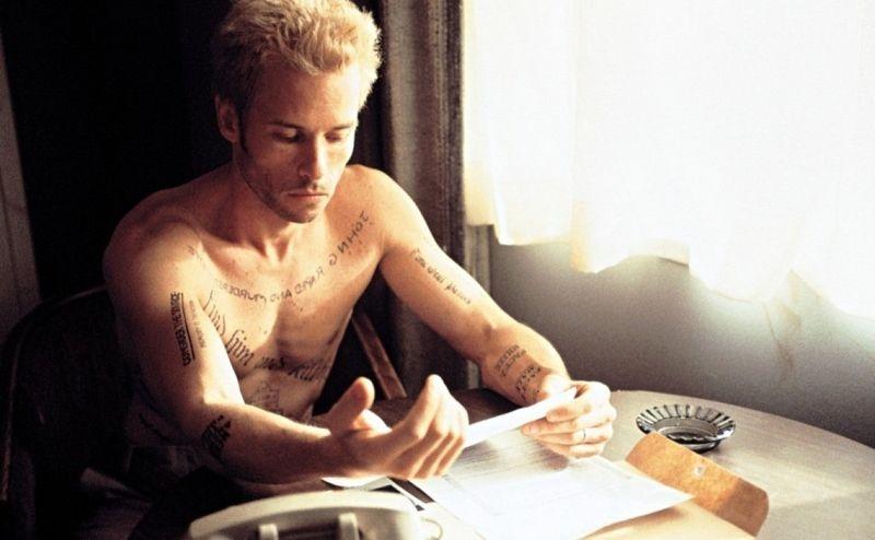 Леонард Шелби изучает свои татуировки и записи