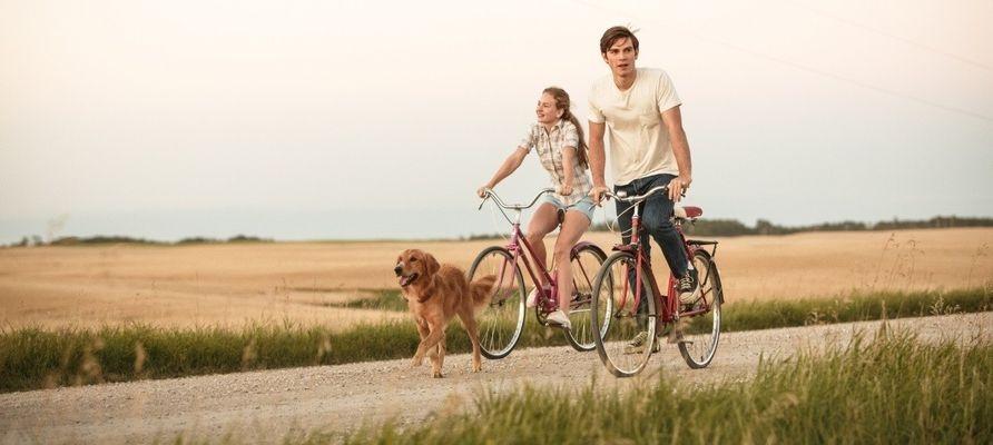 Взрослый Итан катается на велосипеде с девушкой и Бэйли